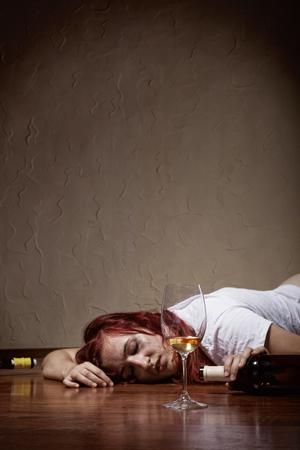 Foto de Drunken young woman lying on the floor. Focus on glass - Imagen libre de derechos