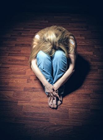 Foto de Sad woman sitting alone in a empty room - Imagen libre de derechos