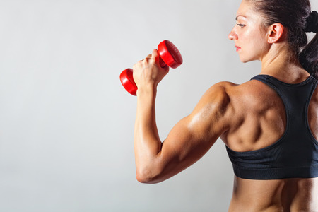 Photo for Fitness woman with barbells on grey background - Royalty Free Image