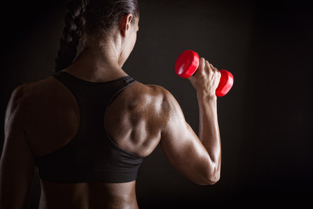 Photo for Fitness woman with barbells on dark background - Royalty Free Image