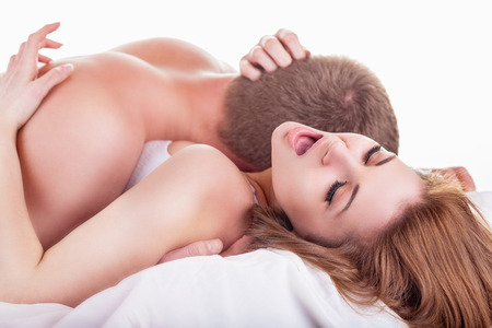 Photo for Young beautiful amorous couple making love in bed on white background - Royalty Free Image