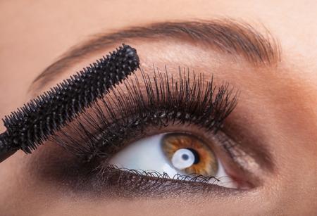 Close-up portrait of a beautiful woman applying mascara for eyelashes