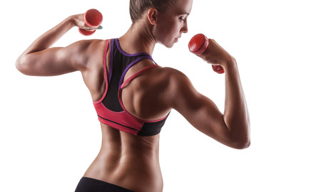 Foto de Muscular fitness girl with weights posing on a white background. Back view - Imagen libre de derechos