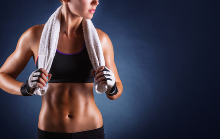 Photo pour Young sports woman after workout with towel on his shoulders on a dark background - image libre de droit