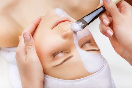 Photo pour Applying facial mask at woman face on a white background - image libre de droit