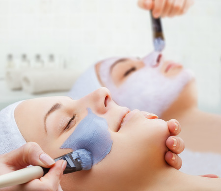 Foto de Use of a face mask to the face two young women in a beauty salon - Imagen libre de derechos