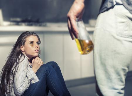 Foto de Woman victim of domestic violence and abuse. Woman scared of a man holding a bottle - Imagen libre de derechos