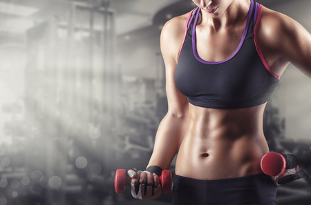 Foto de Training young sports woman in the gym with small weights - Imagen libre de derechos