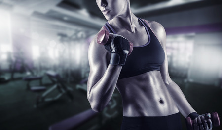 Photo for Close-up of a young woman exercising with weights in the gym - Royalty Free Image