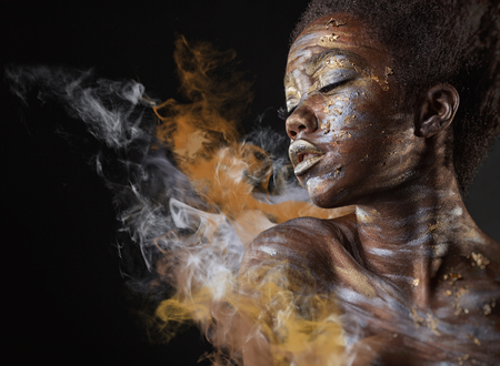 Photo pour Young African American woman with silver and gold make-up and body art on a black background with smoke - image libre de droit