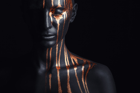 Photo pour Art fashion makeup. An amazing woman with black makeup and leaking gold paint - image libre de droit