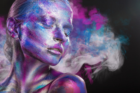 Photo pour Fashion woman with colorful make-up and body art on a black background with multi-colored smoke - image libre de droit