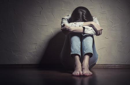 Photo for Young sad woman sitting alone on the floor in an empty room - Royalty Free Image
