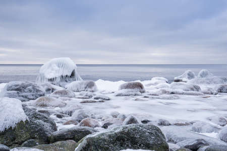 Photo pour Rocky beach on wintertime. Evening light and icy weather on shore like fairy tale country. Winter on coast. Blue sky, white snow, ice covers the land on seaside. Waterside on Juminda, Estonia, Europe - image libre de droit