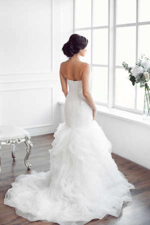 Photo pour Beautiful bride looking at window. Studio shot in white room from behind. Young gorgeous model in brides dress in full length - image libre de droit