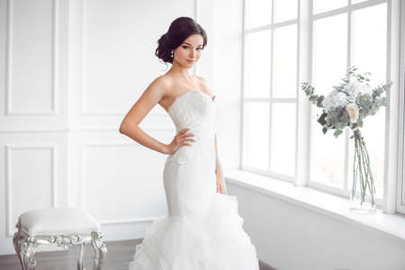 Photo pour Beauty portrait of bride wearing fashion wedding dress with feathers with luxury delight make-up and hairstyle, studio indoor photo. Young attractive multi-racial Asian Caucasian model. Serious sensual beautiful young woman like a bride in white room at b - image libre de droit