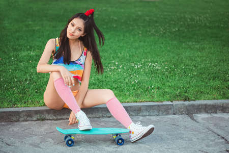 Photo pour Attractive sporty asian woman in swimsuite smiling and sitting with skateboard in city park. Sport and summer holiday concept portrait. Gorgeous playful model posing with board. Young happy girl in bikini looking at camera. - image libre de droit