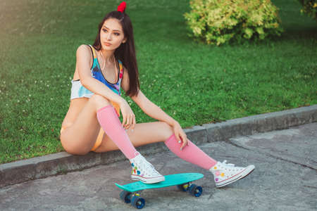 Photo for Attractive sporty asian woman in swimsuite and sitting with skateboard in city park. Sport and summer holiday concept portrait. Gorgeous fashion model posing with board. Young happy girl in bikini looking away. - Royalty Free Image