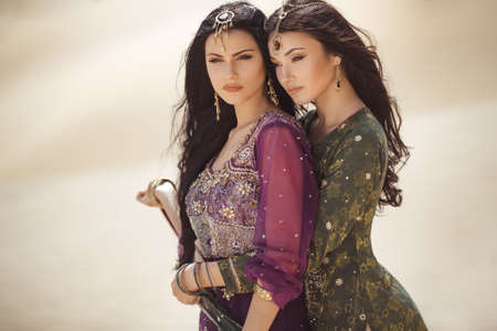 Photo for Travel concept. Adventure of two sisters serious princesses standing in the desert and looking at landscape. Two beautiful mixed race asian caucasianl girls enjoy a joint journey. Creative art fashion portrait shot of two gorgeous attractive models with luxury make-up and hairstyle outdoors in arabian indian dresses. Copy space background on sand dunes. - Royalty Free Image