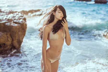 Foto de Romantic young girl in bikini outdoors against ocean background. Portrait of beautiful sensual brunette mixed race Asian Caucasian woman standing on the beach. Slim female model resting on the sea shore and looking at camera. The wind fluttering hair. - Imagen libre de derechos