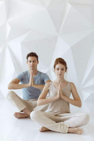 Photo pour Young couple practicing yoga indoors on white abstract polygon background. Young woman and man sitting and meditating with closed eyes together in lotus pose in tantra school. Full length shot. Yoga practice group concept. Calmness and relax, family happiness. - image libre de droit