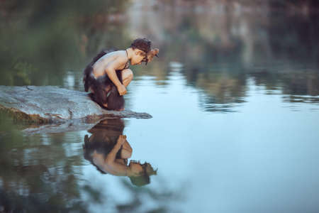 Photo pour Caveman boy sitting on the rock and looking at him self in the water reflection in lake. Evolution survival concept. Creative art fantasy photo - image libre de droit