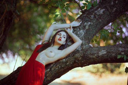 Foto de Sensual sexy fashion model with naked breast resting in fantastical forest. Photo of seductive nude woman in luxury long red dress laying on tree. Multi-racial Asian Caucasian girl. Fashionable toning. Creative computer colors. - Imagen libre de derechos