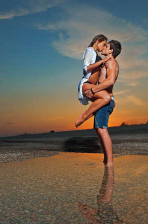 Photo pour young couple kissing at the beach with the sun setting behind them - image libre de droit
