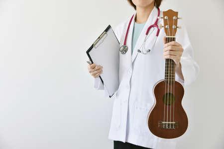 Photo pour Doctor hand holding ukulele (musical instrument), Music therapy concept. (Selective Focus) - image libre de droit