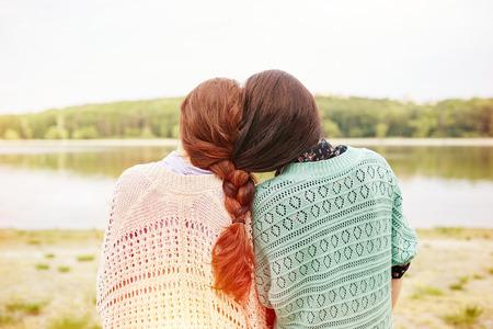 Foto de Two sisters with interwoven hairs looking at the lake. Light leak effect - Imagen libre de derechos