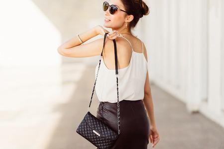 Photo pour Pretty woman wearing sunglasses and bag on his shoulder - image libre de droit