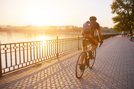 Photo for Young man are cycling road bike by the lake in the park - Royalty Free Image