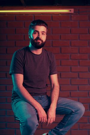 Photo for Cheerful young man in a nightclub is sitting on a bar stool near a brick wall. Neon light - Royalty Free Image