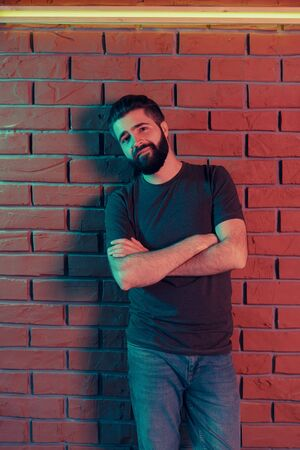 Photo for Cheerful young man in a nightclub at a brick wall. Neon light - Royalty Free Image