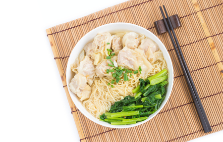 Photo for Wonton and egg noodle soup of Chinese Cantonese style for asian cuisine serving with Chinese cabbage (bog choy) and topped over bamboo plate mat isolated on white background, flat lay (top view) - Royalty Free Image
