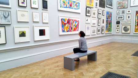 Photo for Art lover viewing art works in Royal Academy - Royalty Free Image
