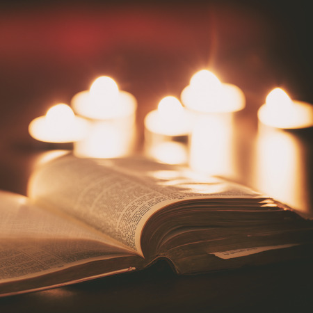 Photo pour Bible with candles in the background. Low light scene. - image libre de droit