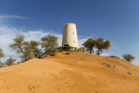 Watch tower on the sand dune that surrounding with trees at Abu Dhabi, UAE.