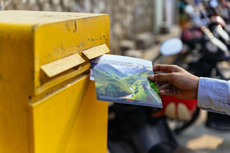Foto de Man right hand sending postcard in yellow post box in summer in Sa Pa, Vietnam. - Imagen libre de derechos