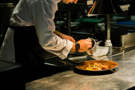 Photo for Chef plating dish on kitchen counter while recording at kitchen hotel. - Royalty Free Image
