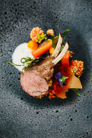 Photo for Modern French cuisine: Close up roasted Lamb neck & rack served with carrot, yellow curry served in black stone plate. - Royalty Free Image