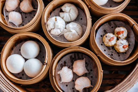 Photo for Closeup top view of Dim sum set: Barbecued pork bun, Shrimp dumpling, Sweet cream buns, Shrimp shumai topping with goji berry served in steamer baskets. - Royalty Free Image