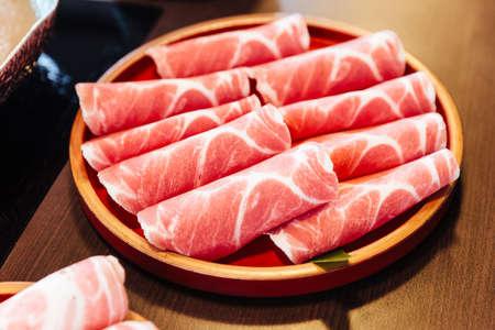 Photo for Premium Rare Slices Kurobuta (Black Pig) pork with high-marbled texture on circle wooden plate served for Sukiyaki and Shabu. - Royalty Free Image