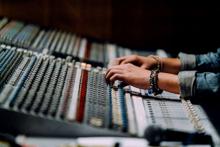 Photo for Professional hands nearby soundboard are mixing sounds by audio mixer control panel with buttons and sliders in recording studio. - Royalty Free Image