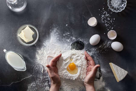 Foto per Woman hands knead dough on table with flour - Immagine Royalty Free