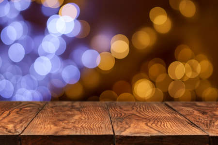 Foto per wooden table with yellow holiday lights on background - Immagine Royalty Free
