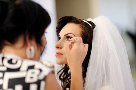 Photo pour Stylist makes makeup bride on the wedding day - image libre de droit