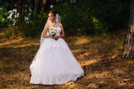 Foto de Beautiful bride with bouquet of flowers outdoor - Imagen libre de derechos