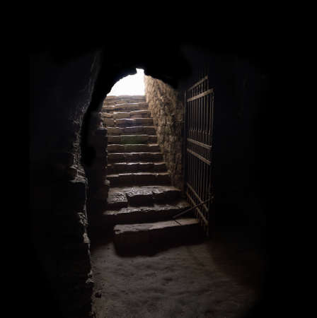 Photo for Arc fort passageway from cold damp Blackness to glow Light with rusted iron grate cell. Gaol rugged ominous shadow solid hallway with upward leading to day sunlight with space for text on sky backdrop - Royalty Free Image