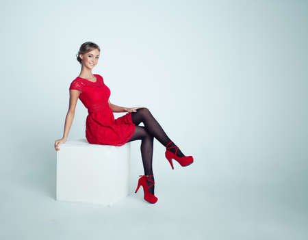 Foto de Happy Woman in Red Dress on White Background - Imagen libre de derechos